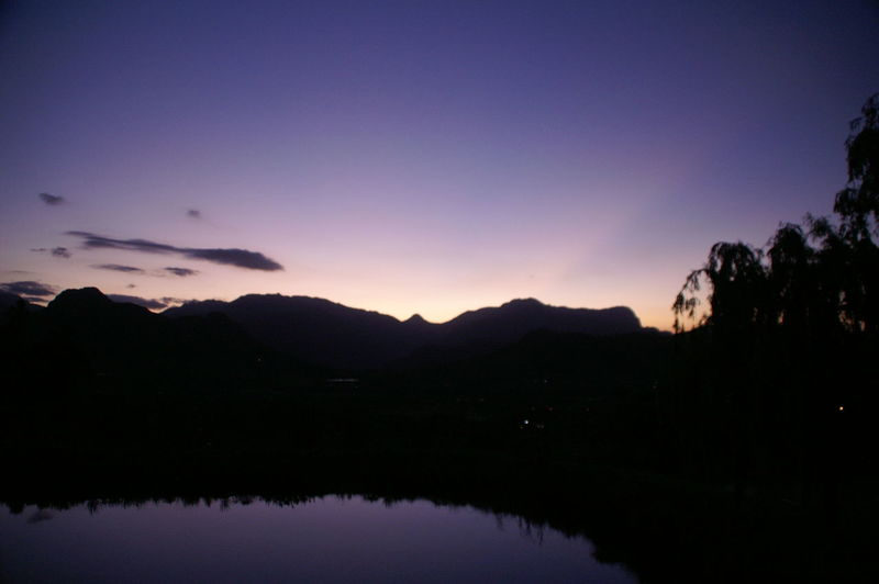 Scenic view of lake and silhouette mountains against sky at sunset