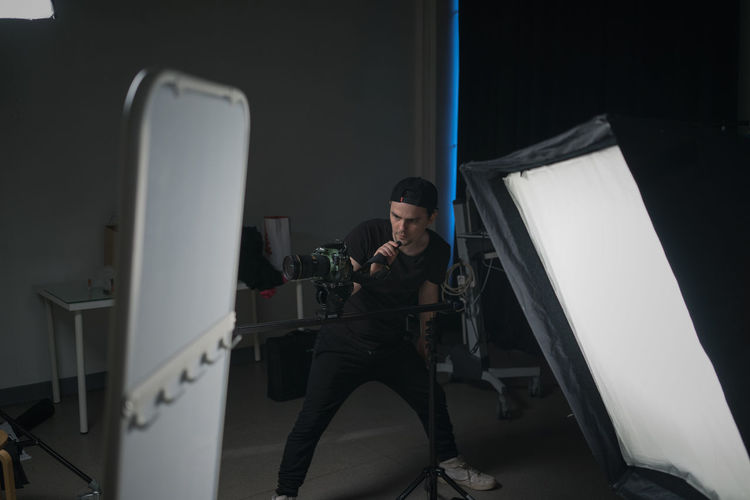 Young Man Operating Camera In Studio