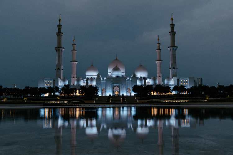 Reflection of illuminated mosque in lake at night