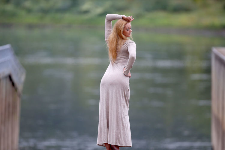 Side view of woman standing against water