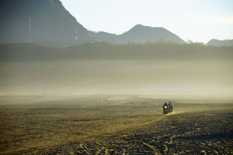 People Riding Motorcycle On Field During Foggy Weather