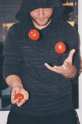 Portrait Of Man Playing With Tomatoes