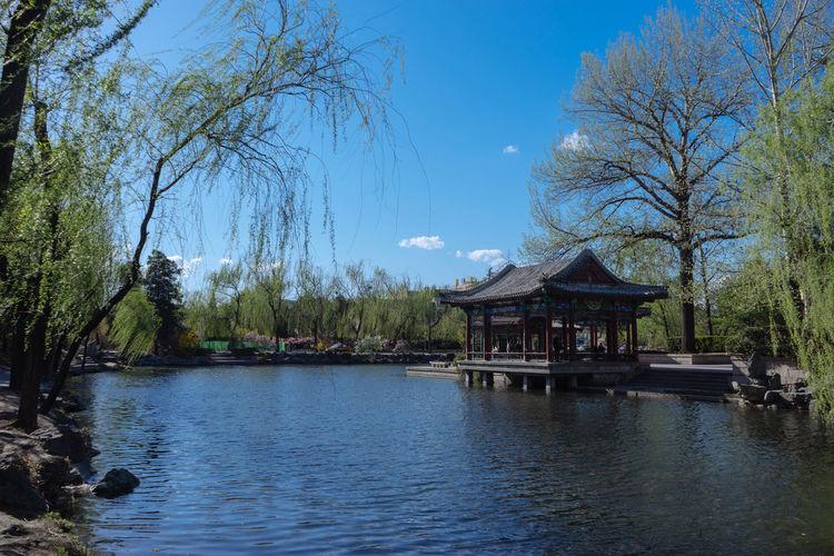 Gazebo in lake against blue sky