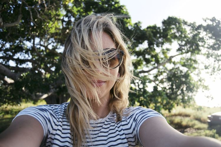 Taking a selfie on a hike Travel Adventure Blond Hair Close-up Day Explore Focus On Foreground Front View Nature One Person Outdoors People Portrait Real People Selfie Sunglasses Tree Young Adult Young Women