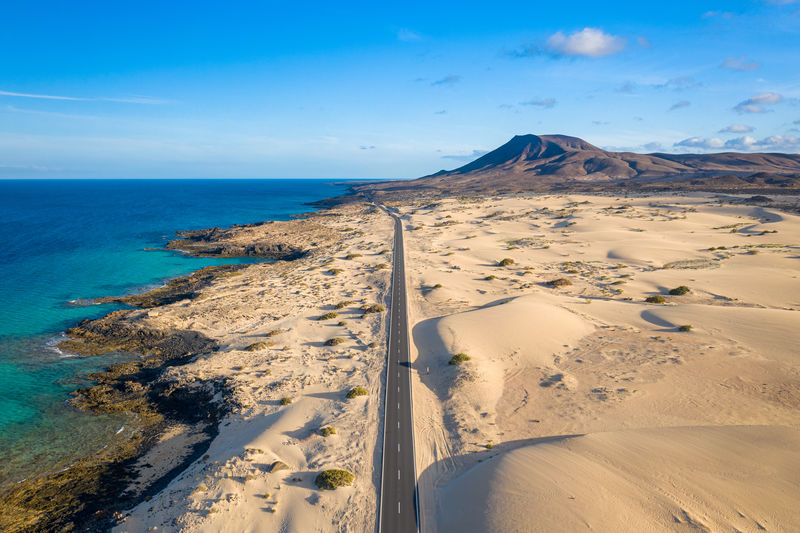 High angle view of road going through Corralejo dunes nature park in Fuerteventura. Coast Travel Landscape Fuerteventura Island Holiday Ocean Aerial Desert Beach Sand Sea View Shore Tourism Corralejo Nature Summer Scenic Coastline Road Vacation Adventure Beautiful Dry Canary Atlantic Water Highway Background Dune SPAIN Seascape Tranquil Dunes Destination Europe Canarias Sun Scenery Sky Street Volcano Above Arid Drone  Panorama Sunny Perspective Sandy
