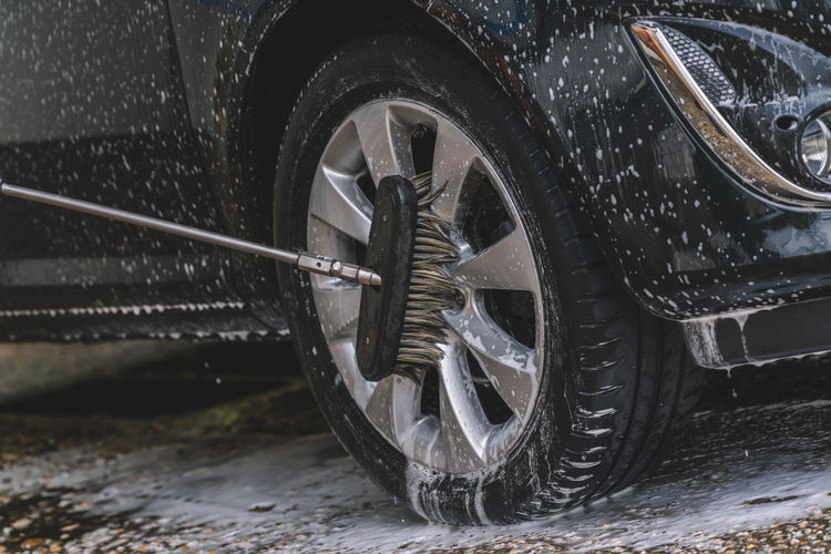 Cleaning Equipment On Tire Of Car During Wash