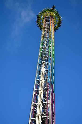 Low angle view of drop tower against blue sky