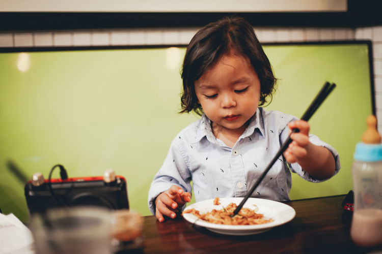 Child Childhood Real People Front View Food And Drink Indoors  One Person Table Food Holding Headshot Restaurant Eating Eating Utensil Innocence Lifestyles Females Kitchen Utensil Casual Clothing Meal