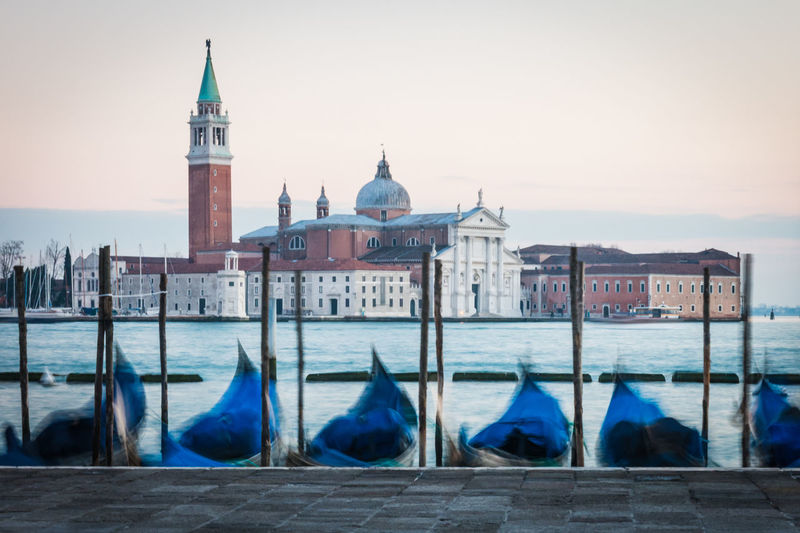 View of the church San Giorgio Maggiore with gondolas lined up in St Mark's Bay, Venice, Italy Architecture Blue Blue Eyes Blue Sky Building Exterior Built Structure Cathedral Church City Dome Famous Place Gondola Italy Long Exposure,monochrome Place Of Worship Religion San Giorgio Maggiore Sky Spirituality Travel Destinations Water