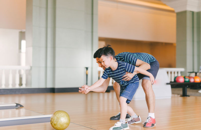Asian family having fun at bowling club Ball Bowling Bowling Alley Boy Boys Casual Clothing Child Childhood Father Flooring Full Length Indoors  Lerning Lifestyles Males  Men Parent Particle Playing Pre-adolescent Child Real People Son Sport Teach Young Adult