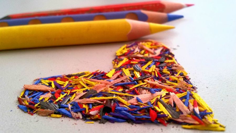 Close-up of multi colored pencils by heart shaped shavings on table