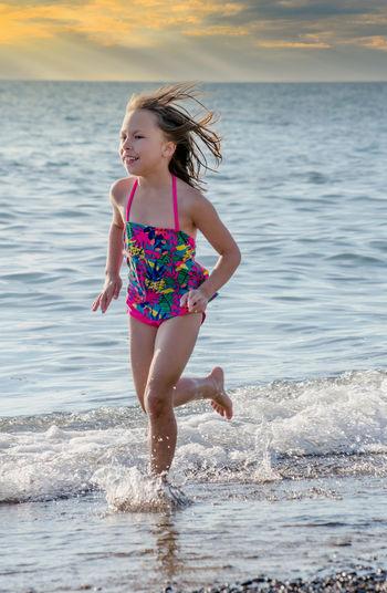 Full length of woman on beach against sea