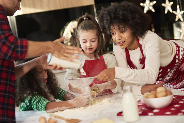 Family preparing food on table during christmas