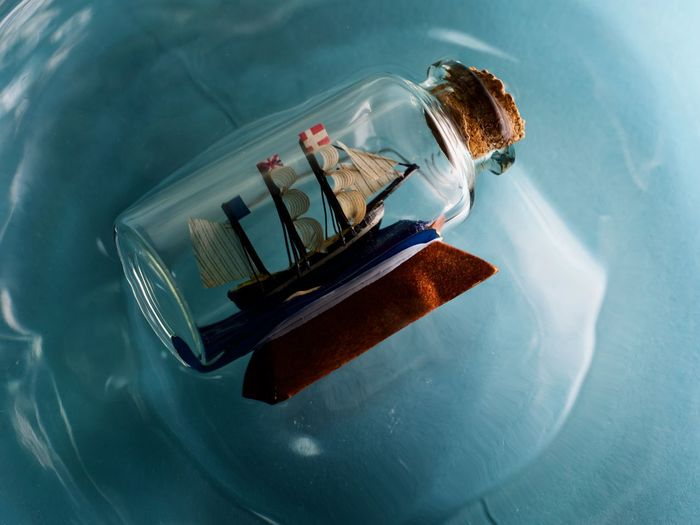 High angle view of ship in a bottle floating on blue water