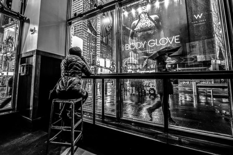 """""""Behind the Glass"""" Black And White Blackandwhite Girl Indoors  Men New York Night Lights One Person Rain TimesSquare Umbrella The Street Photographer - 2017 EyeEm Awards EyeEm Selects Fresh on Market 2017 Stories From The City The Art Of Street Photography My Best Photo"""