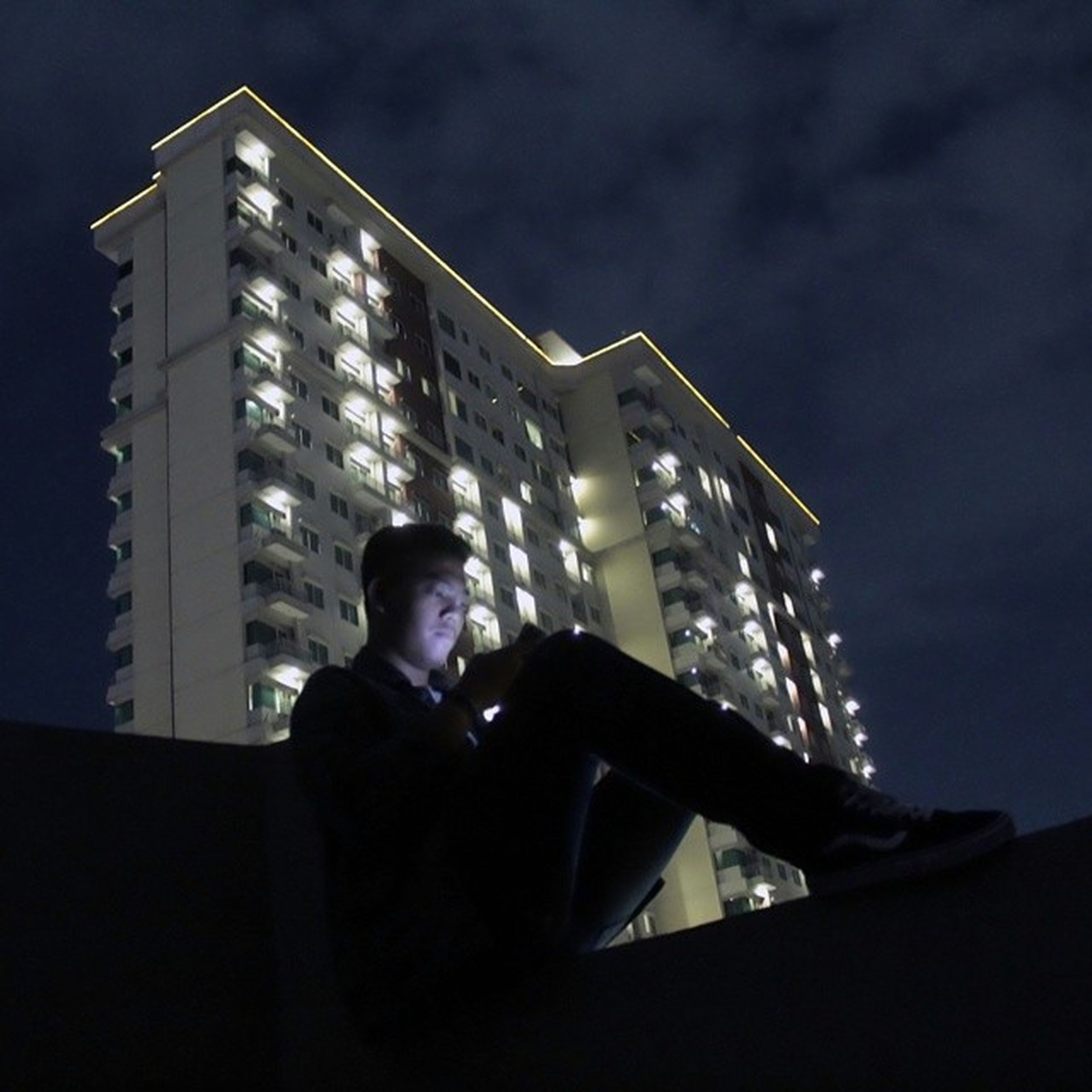 lifestyles, leisure activity, built structure, architecture, young adult, night, young men, headshot, low angle view, building exterior, sky, waist up, photographing, photography themes, side view, men, person, sitting