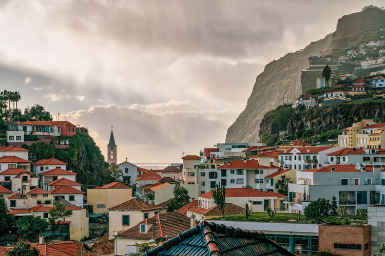 Townscape of a mountainside harbor town with heavy clouds during oncoming sunset