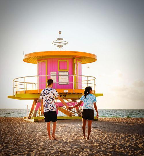 Lifeguard Hut Caribbean Miami Miami Beach Man Woman Sea Full Length Togetherness Beach Men Standing Sand Rear View Sky Architecture Lifeguard Hut Shore Calm Sandy Beach Pebble Beach Lifeguard  Horizon Over Water Surfer Seaside Hooded Beach Chair Ocean Clear Sky Wave Friend