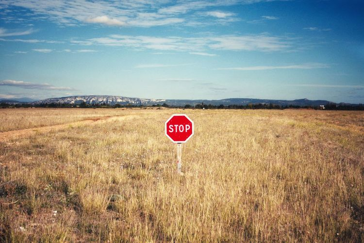 Stop sign on grassy field against sky