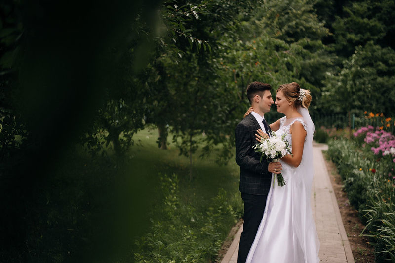 Newlywed couple looking at each other while standing against trees