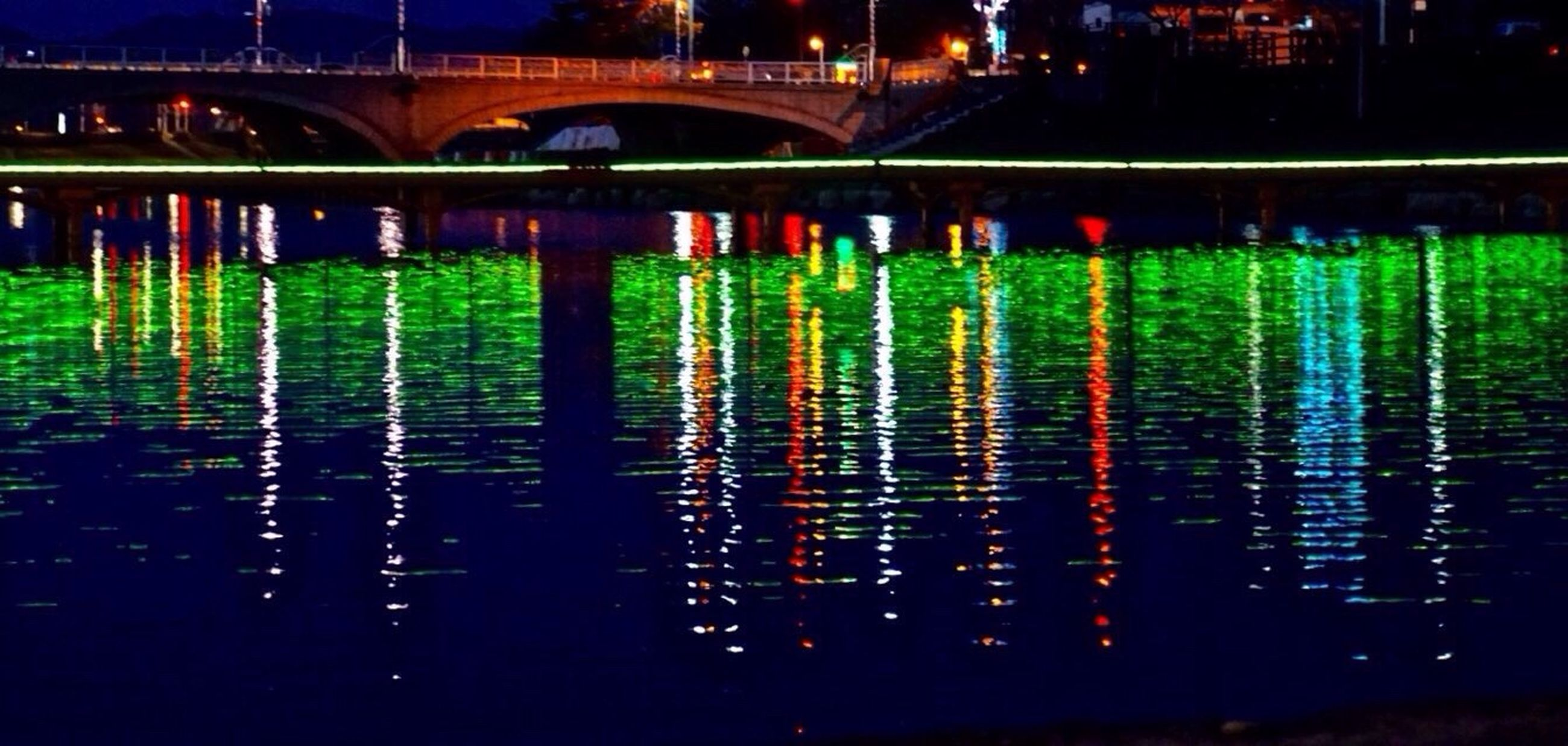 illuminated, night, water, reflection, built structure, architecture, river, waterfront, building exterior, city, outdoors, no people, bridge - man made structure, light - natural phenomenon, lake, light, in a row, connection, multi colored, dark