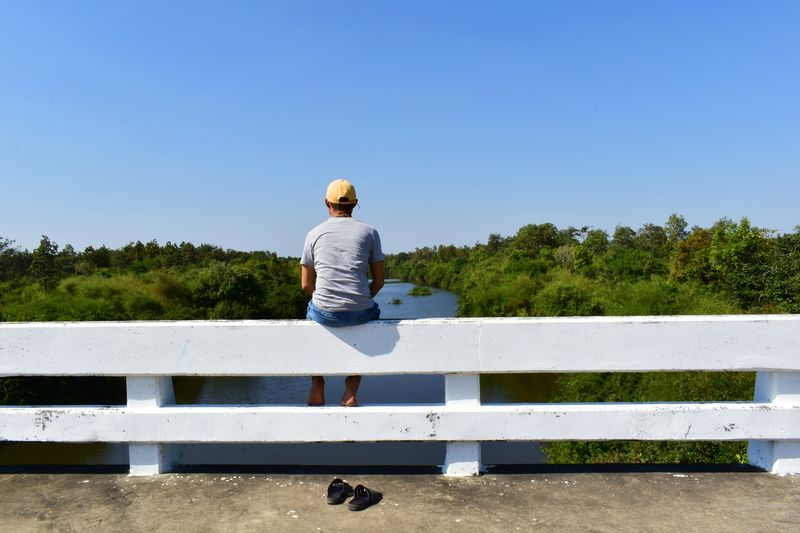 Rear view of man on bench against sky