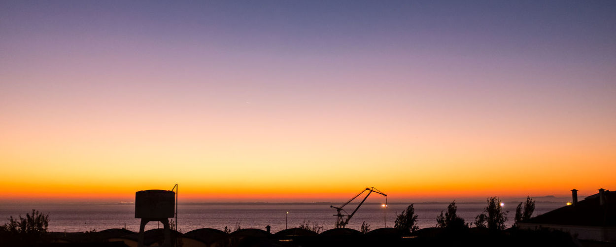 Silhouette storage tank and crane by sea against clear sky during sunset