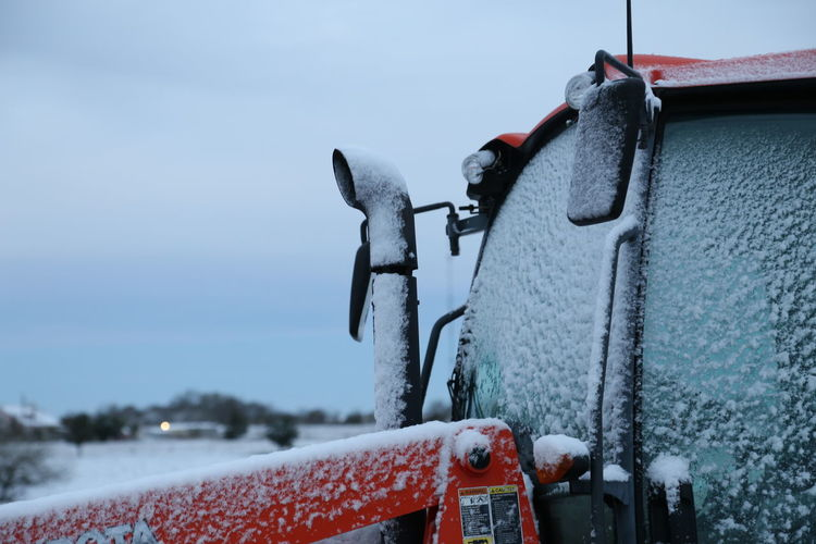 Close-up of snow on car against sky during winter