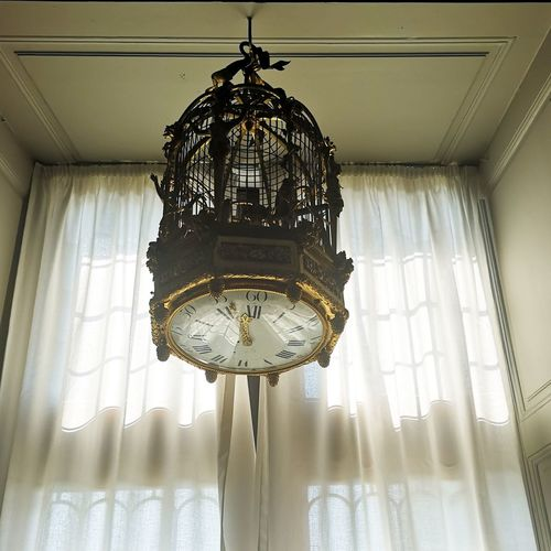 Low angle view of chandelier hanging on ceiling of building