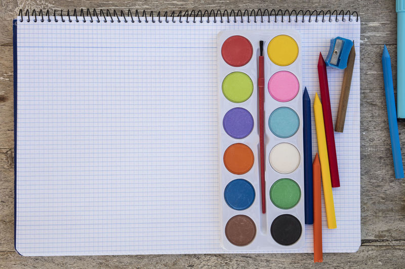 Directly above shot of multi colored pencils and spiral notebook on table