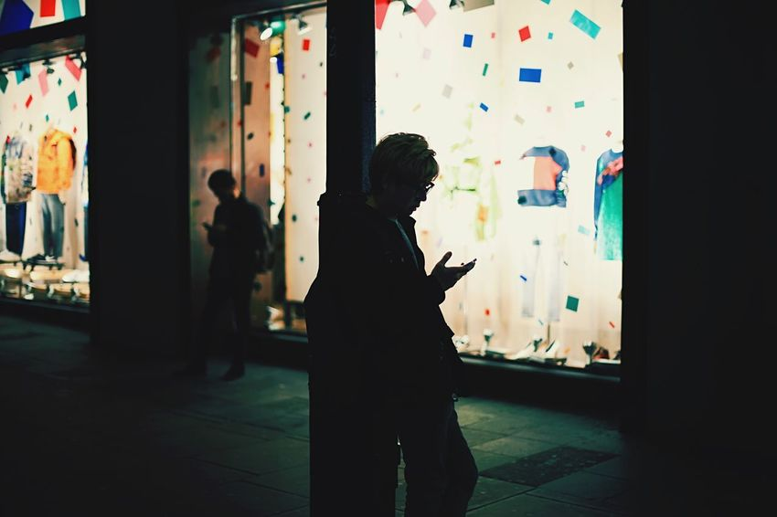 Forever looking at phone screens Oxford Street  Lamp Post Street Light Streetlight Lampost Waiting Around Waiting Shadow Light Night Nightlife Shop City London Distracted IPhone Screen Phone Real People Indoors  Women Standing Men Silhouette Two People Going Remote