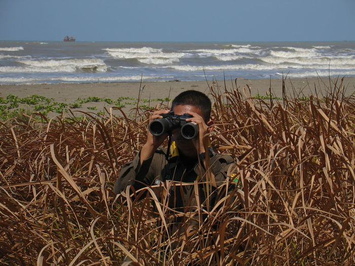 Portrait of man photographing on beach