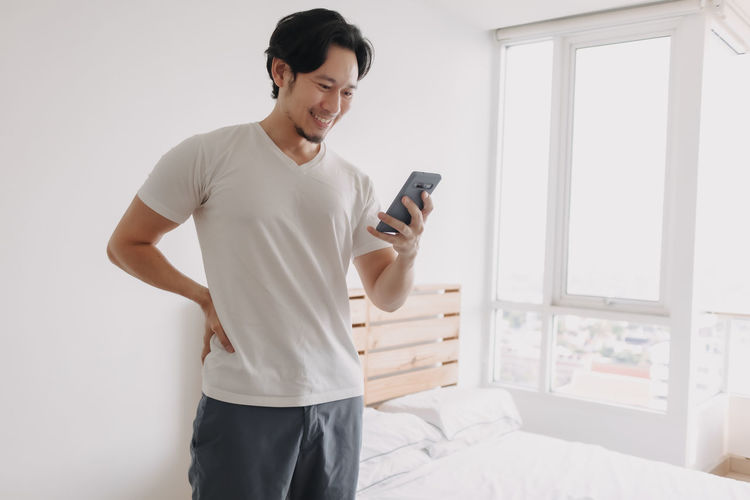 Young man using mobile phone while standing on bed
