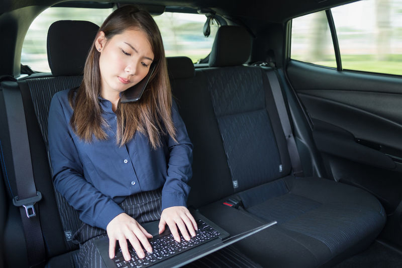 Businesswoman with laptop using phone in car