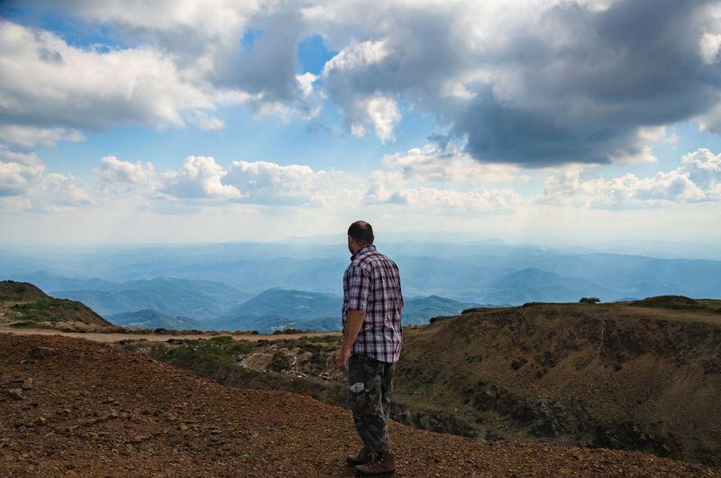 Man dressed for hiking is walking on top of kopaonik mountain, serbia and watching landscape