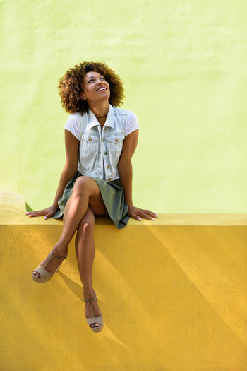 Young woman looking up while sitting against yellow wall