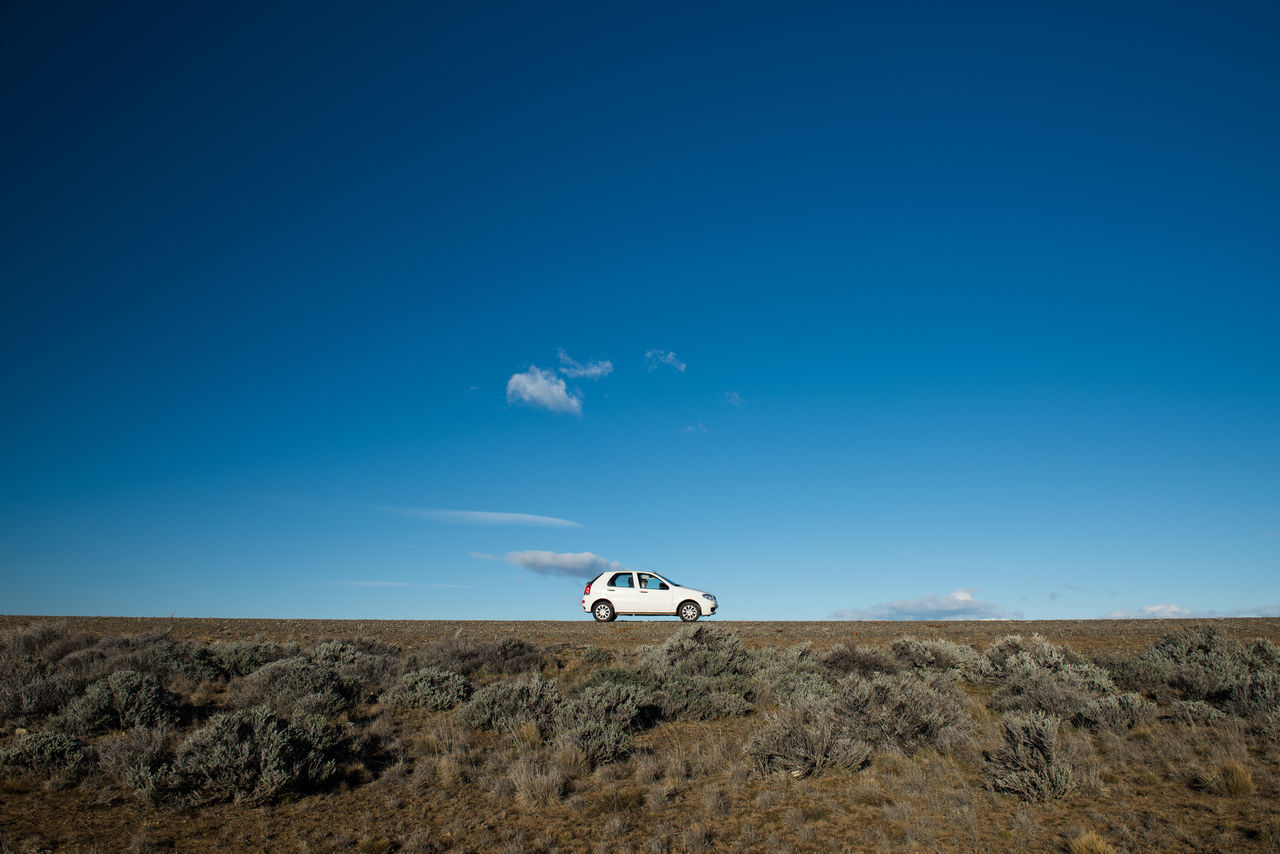 blue, transportation, landscape, mode of transport, nature, beauty in nature, land vehicle, horizon over land, outdoors, day, scenics, off-road vehicle, no people, arid climate, sky, desert, clear sky