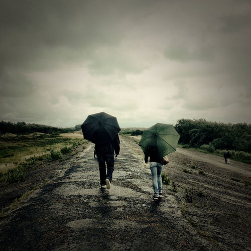 Rear View Of People With Umbrella Walking On Road