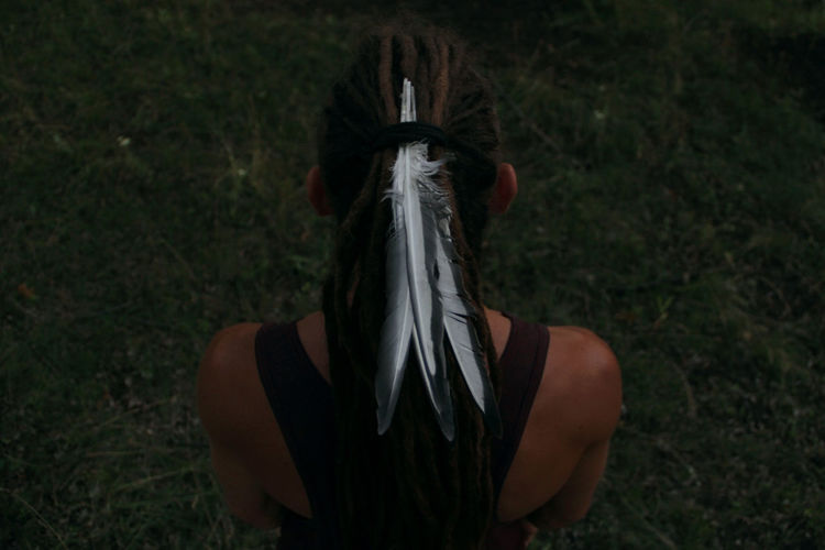 High angle view of feathers in dreadlocks of woman standing on field