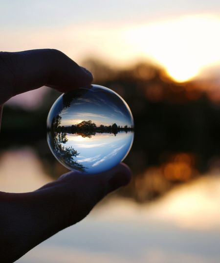 Close-up of hand holding glass of crystal ball against sunset sky