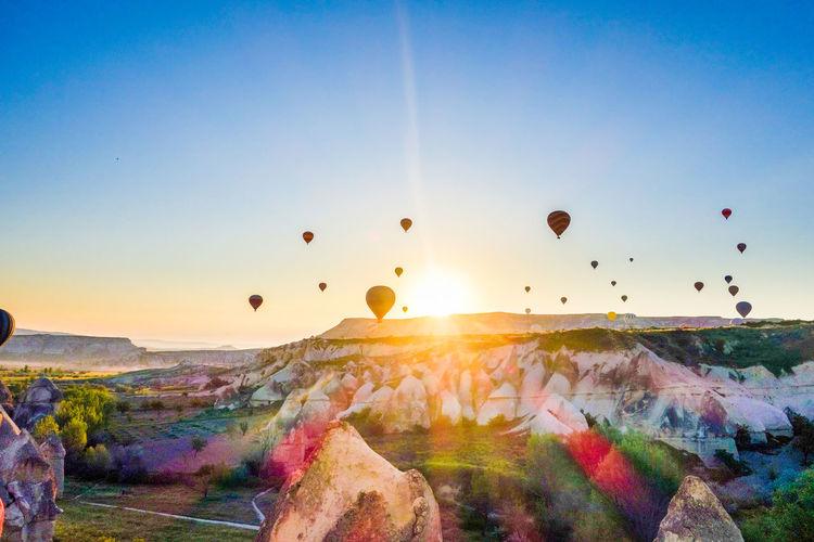 Hot air balloons flying over cappadocia against clear sky