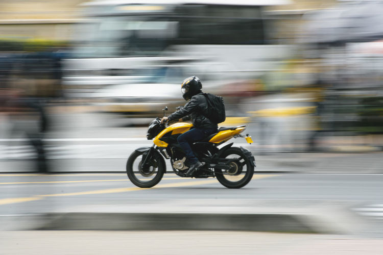 Blurred motion of person riding motorcycle on road