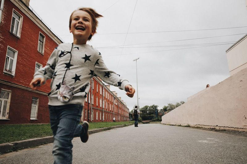 Happy boy running on road in city