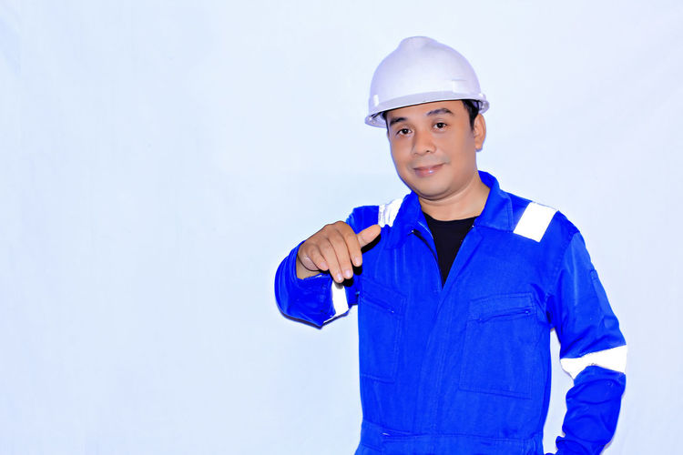 Front View Looking At Camera One Person Helmet Headwear Portrait Blue Waist Up Studio Shot Smiling Copy Space Indoors  Standing Males  Protection Men Hardhat  Lifestyles Hat
