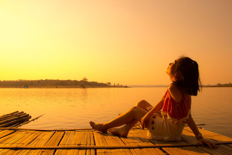 Woman sitting on wooden raft in lake against clear sky during sunset