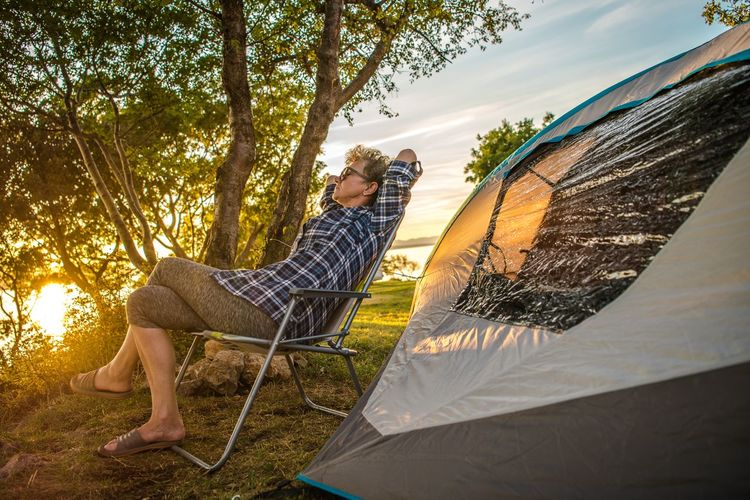 Senior woman relaxing on chair by camping tent during sunset