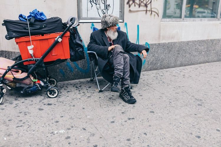 The Street Photographer - 2017 EyeEm Awards Full Length One Person Casual Clothing Sitting City Outdoors Day Building Exterior Lifestyles Built Structure One Man Only People Adult Only Men Adults Only Warm Clothing Young Adult