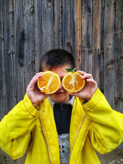 Boy Holding Orange While Standing Against Wooden Fence