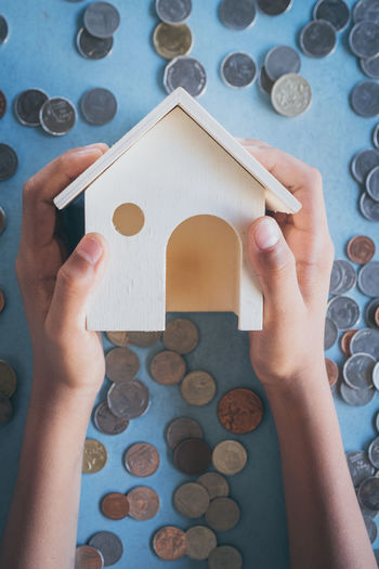 Cropped Image Of Hands Holding Model House Over Coins