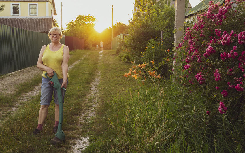 Full length of woman holding metal detector while standing on field